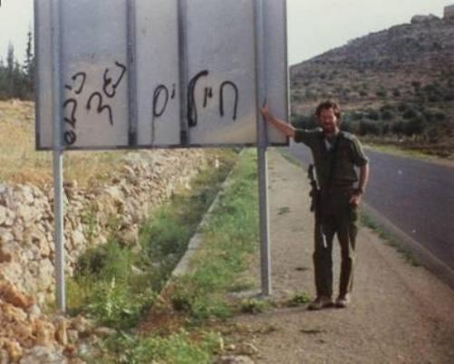אמנון בתקופת שרותו הצבאי ליד שלט עם כתובת שמאלנית.