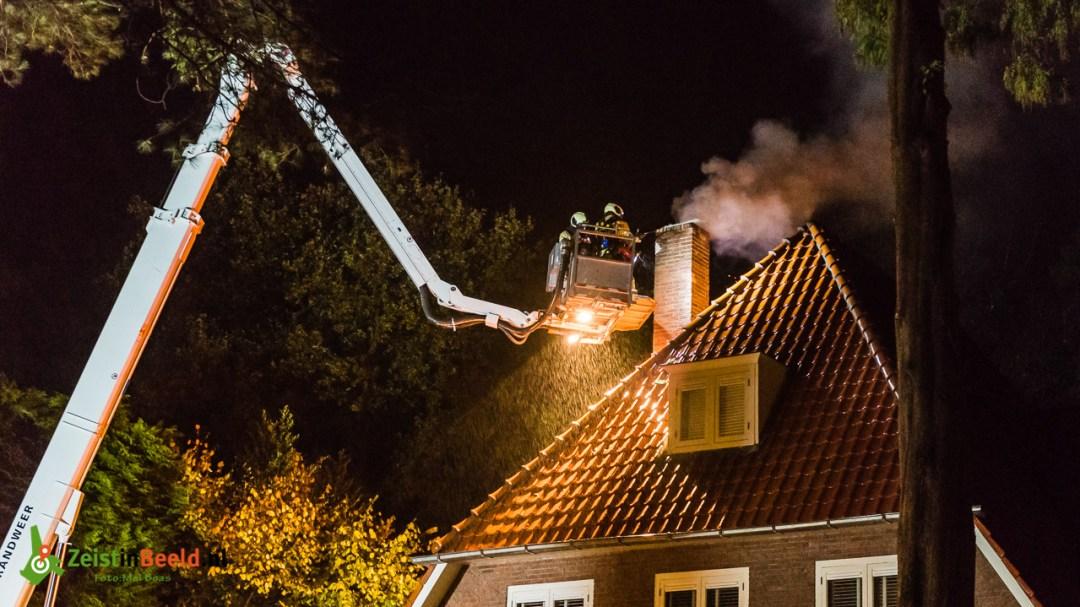In de stromende regen werd de schoorsteenbrand bestreden door de mannen van de Brandweer Zeist