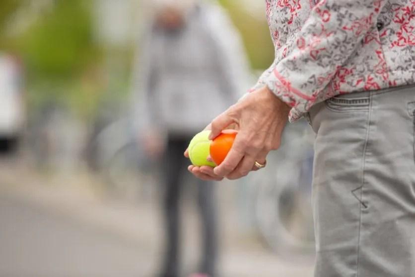 Detailaufnahme: eine Frau hält einen gelben und einen orangen Ball in der Hand.