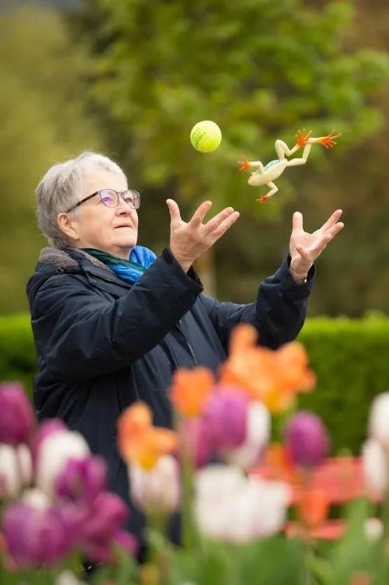 Koordinationstraining im Freien: Eine Seniorin wirft gleichzeitig einen Gummifrosch und einen Ball in die Luft.