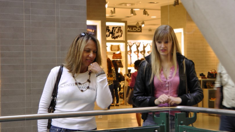 """Some shoppers looking at """"Fragile"""" by Roadsworth and Brian Armstrong at the Eaton Centre."""