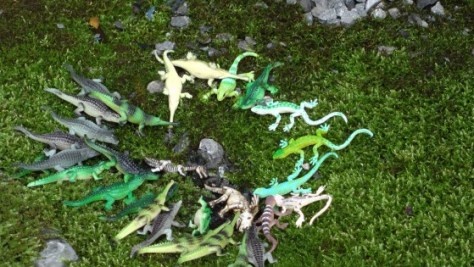 Some dollar store plastic crocodiles hanging around a rock.