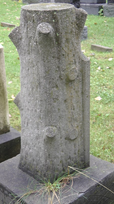 The back of a monument looking like a log at The Baron de Hirsch Cemetery