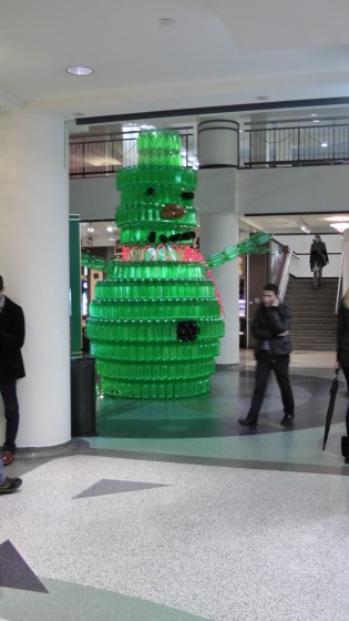 A different perspective on a giant green snowman made out of recycled soda bottles.