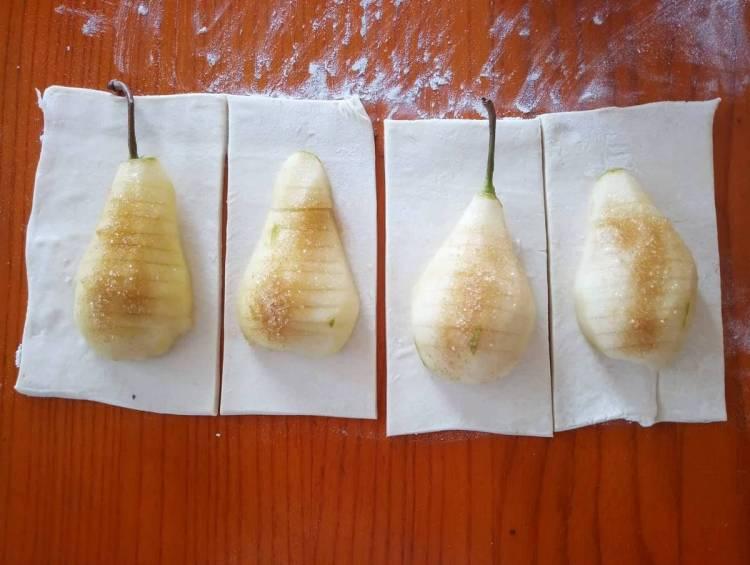 Тісто розгортаємо і розрізаємо на прямокутники, на них кладемо половинки груш
