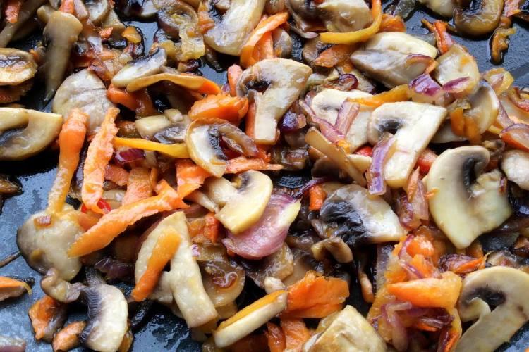Додаємо до грибів дрібно порізану цибулю, моркву та обсмажуємо все разом