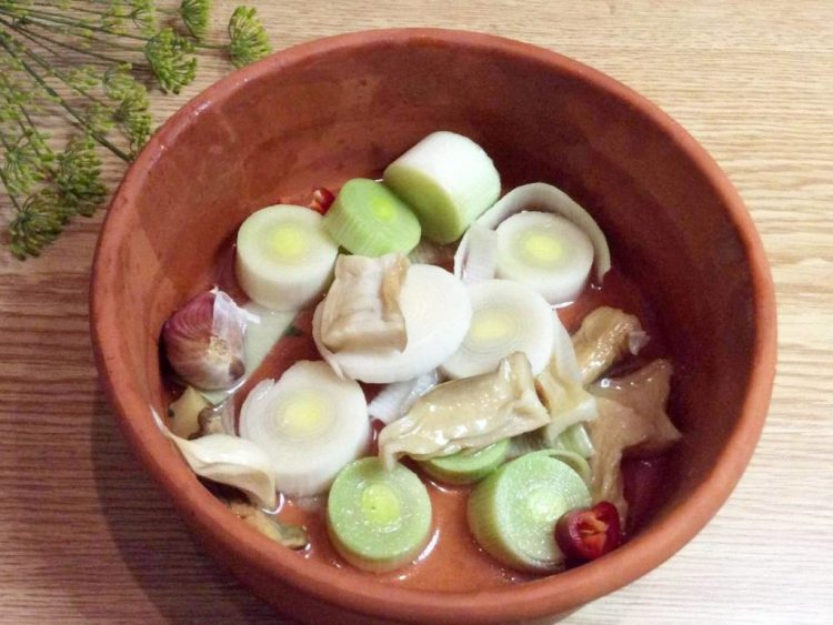 На дно ємності, в якій буде готуватися м'ясо, укладаємо порізану цибулю порей, гриби, кілька дзюбочків не очищеного часнику
