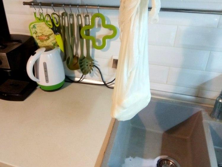 Викладаємо замерзлі брикети кефіру та сметани на марлю та підвішуємо, щоб стікла рідина