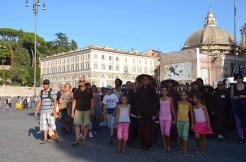 Ill maestro guida la meditazione camminata, al riparo dei raggi del sole col suo copricapo tradizionale e circondato dai bambini