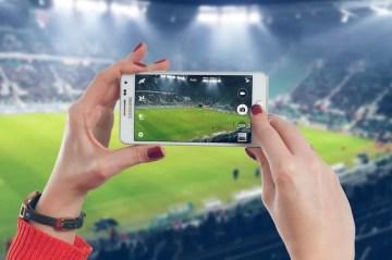 con il telefono smartphone allo stadio a vedere la partita di calcio