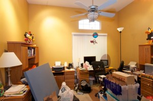 Large cluttered office with several desks. A professional organizer can help.
