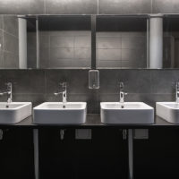 Faucets with washbasin in public restroom in grey colors.