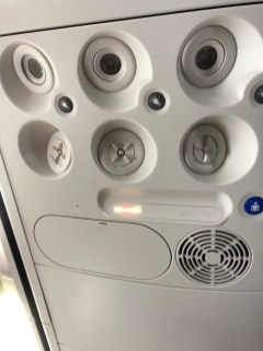 Air vent and lighting on the ceiling above the seat