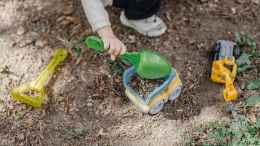 little kid putting sand in toy car using little shovel