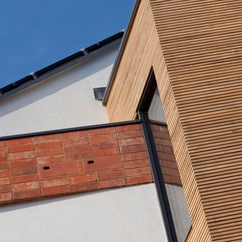 The outside of zero carbon house, Birmingham showing homes for two birds within the red bricks