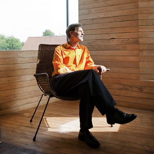 John Christophers, architect of zero carbon house, Birmingham sits in the studio in an orange shirt