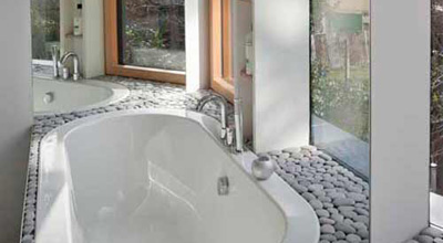 Bathroom at zero carbon house, Birmingham showing bath and taps and pebbles