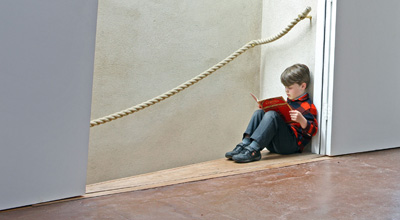 Theo reads a book sitting at the top of the stairs in zero carbon house, Birmingham with the hemp stair rail also in view