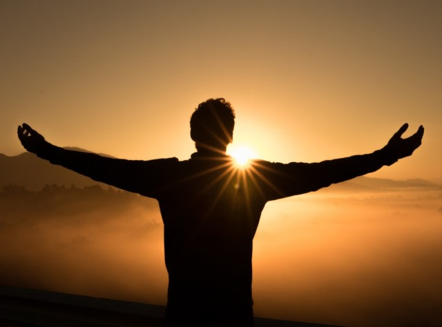 A man standing with open arms in rejoice