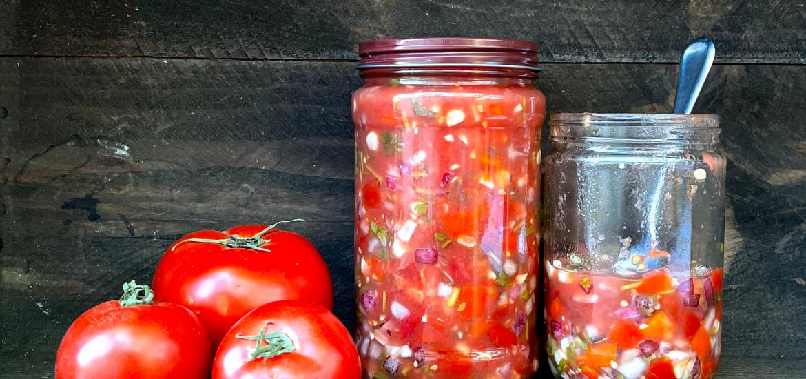 Three tomatoes and two jars of salsa on a brown wooden background. One larger jar is full. The other smaller jar is half full. The lid is off and a spoon is sitting in the jar.