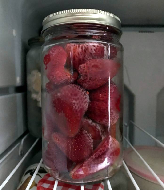 glass jar filled with frozen fruit