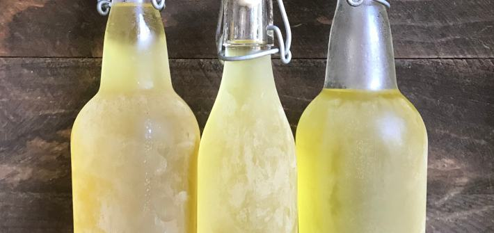three bottles of limoncello made out of lemon peels to use up all the food scraps