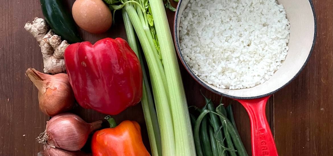A pot of rice and various vegetables arranged on a tabletop. These will go into fried rice, a very frugal and versatile dish.