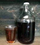 a glass and a glass jug of iced tea on a dark brown background