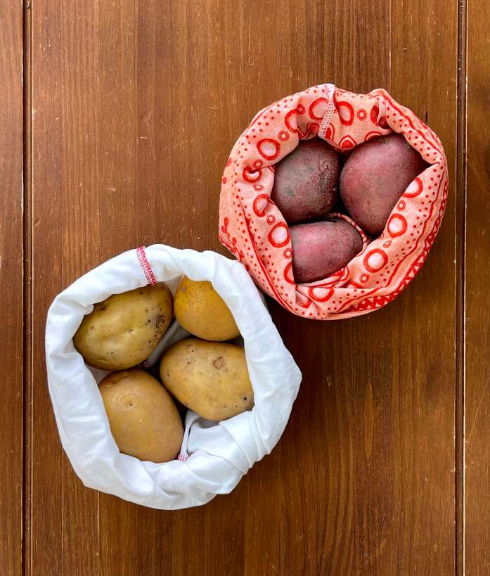 Two cloth bags with potatoes to make sourdough-potato focaccia. The top orange and red bag contains three red potatoes. The bottom white bag contains four yellow potatoes. The bags sit on a dark wood tabletop.