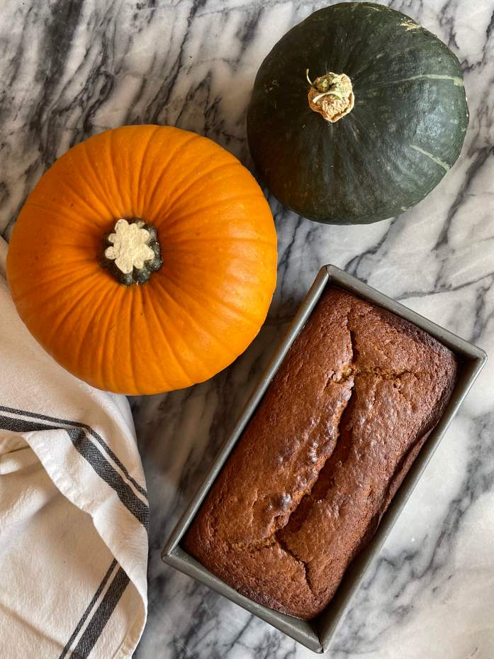 A loaf of pumpkin sourdough quick bread in a loaf pan on a white and grey marble background. Above it are a sugar pie pumpkin and a kabocha squash.