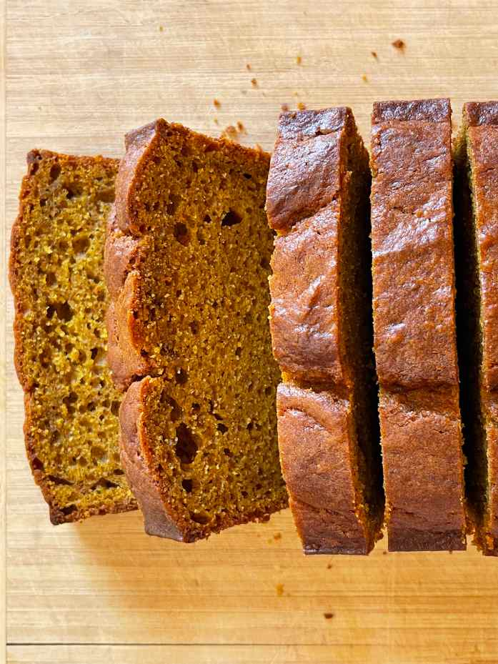 Close up of slices of pumpkin sourdough quick bread on a wooden cutting board