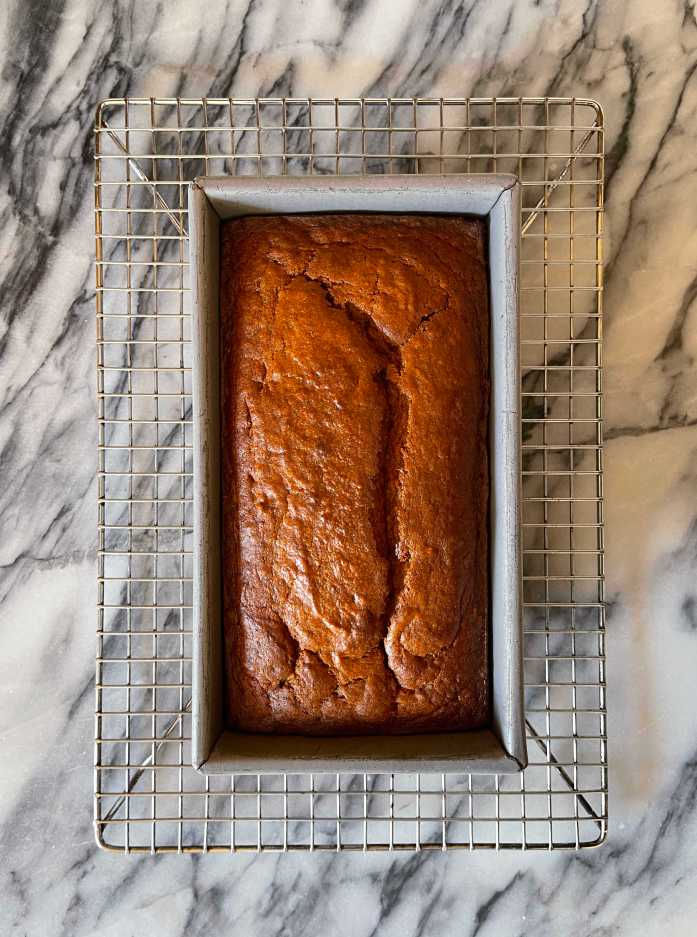 Pumpkin sourdough quick bread in a metal loaf pan cooling on a metal rack sitting on a marble background