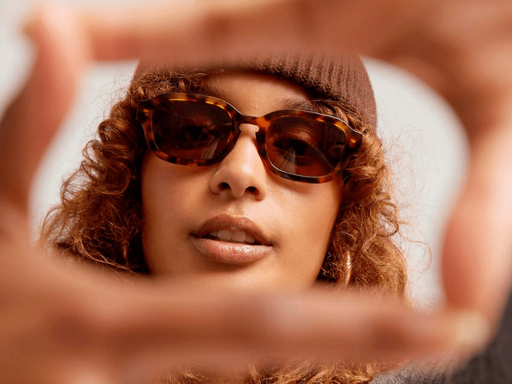 Woman holding up her hands in Colorful Standard sustainable sunglasses