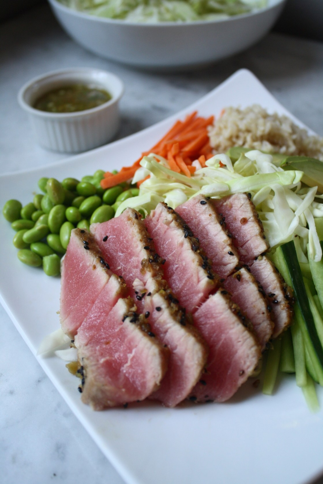 Wasabi Crusted Ahi Tuna set on a plate with edamame, carrots, rice and cabbage | Zestful Kitchen