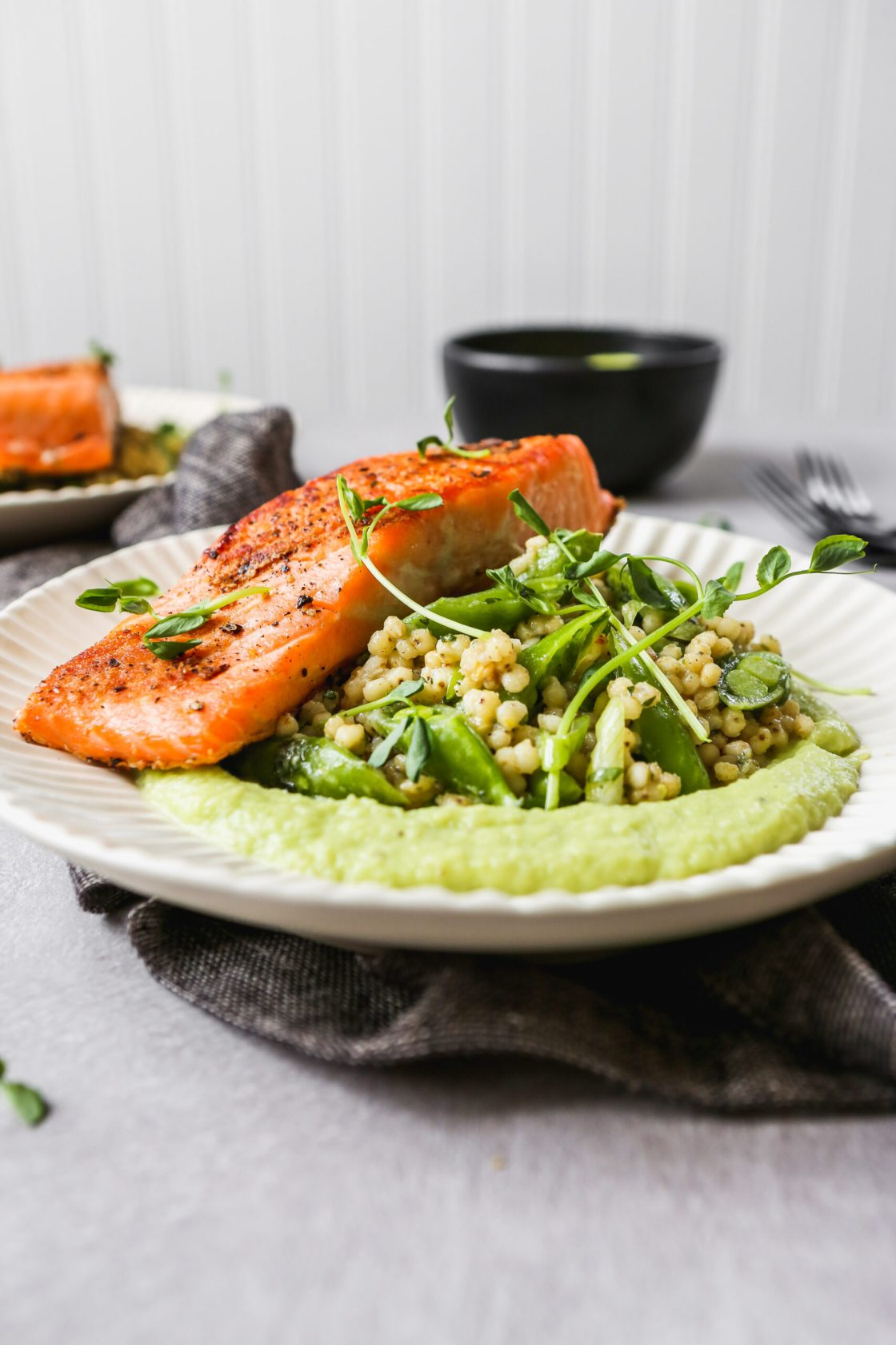 Pan seared salmon on white plates with green sauce and grain salad, set on a gray background.
