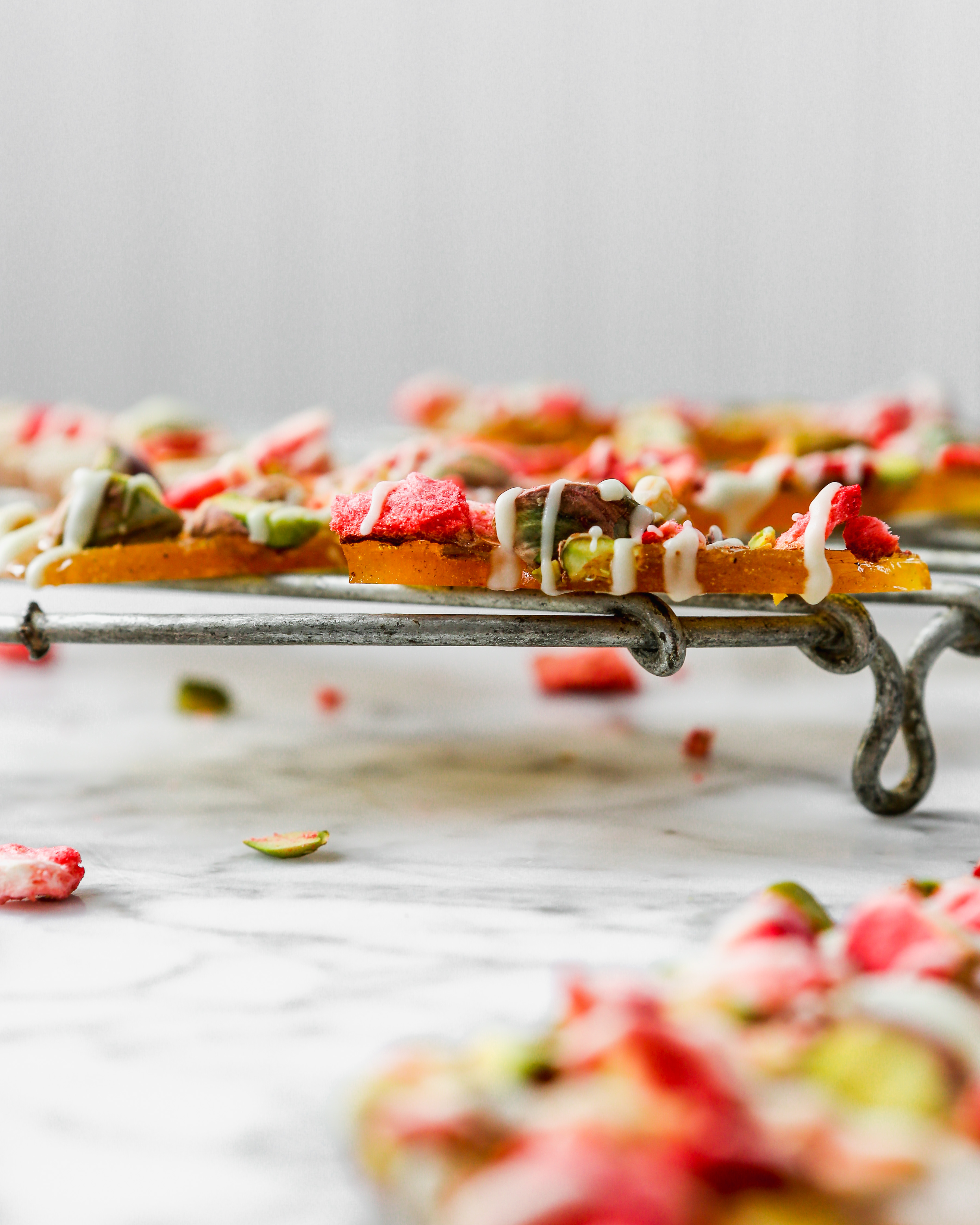 Pistachio, Strawberry, White Chocolate & Cardamom Brittle layered on a wire rack on a marble table | Zestful Kitchen