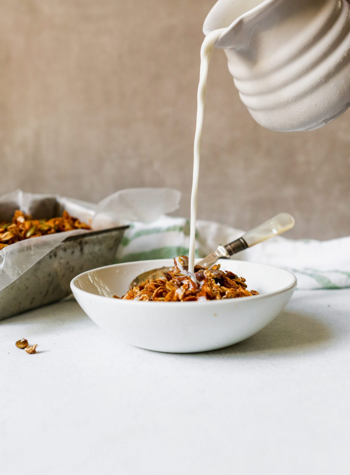 Homemade granola in a white bowl with milk pouring into bowl.