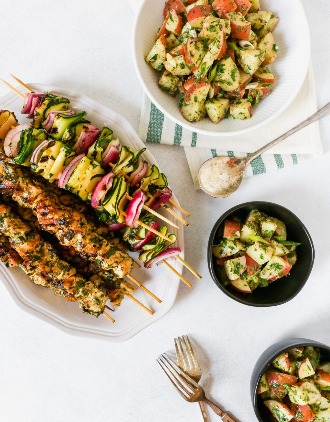 White platter filled with grilled chicken and vegetable skewers, red potato salad, and individual bowls of potato salad on a while background. Summer dinner photography