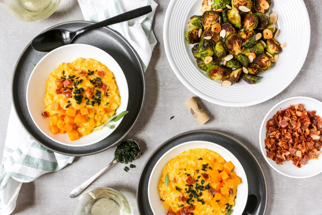 Dinner table with bowls of butternut squash risotto, roasted brussels sprouts, prosciutto, and wine.