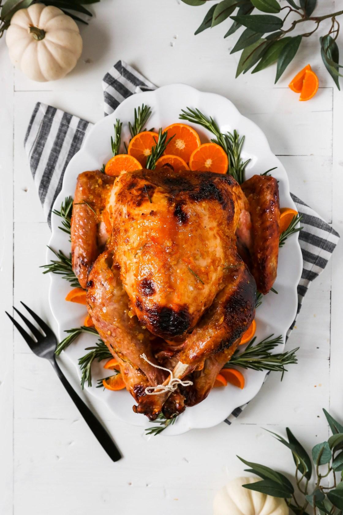 photograph of a whole glazed roast turkey on a large white platter