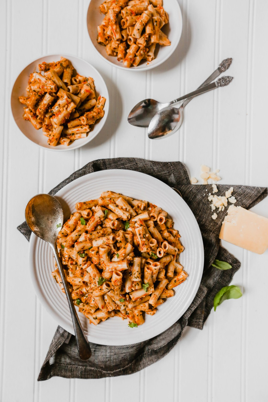 Trapanese pesto pasta piled into a white bowl with a dark napkin around it