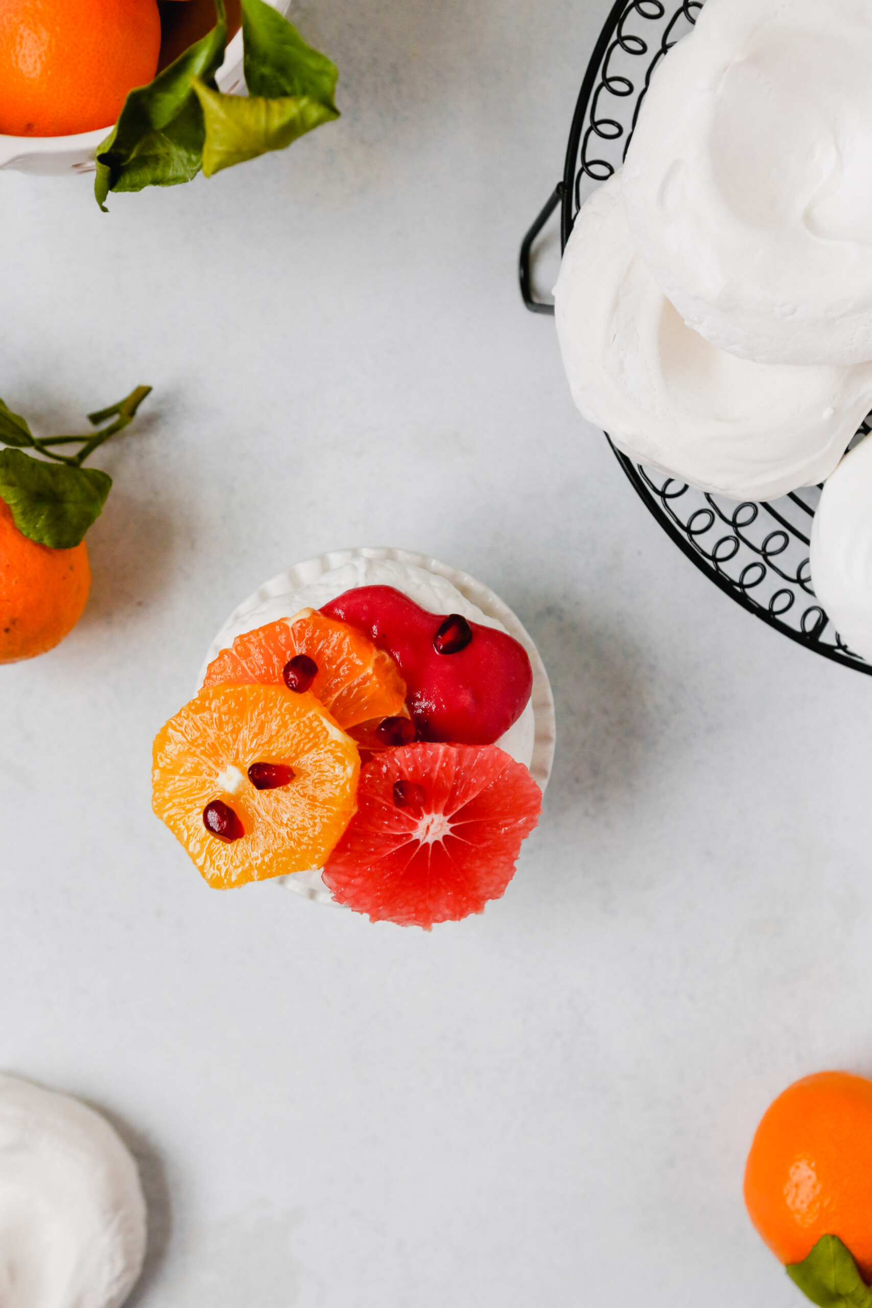 Photography of mini pavlova topped with pink cranberry curd, citrus fruit, pomegranate seeds and spices.