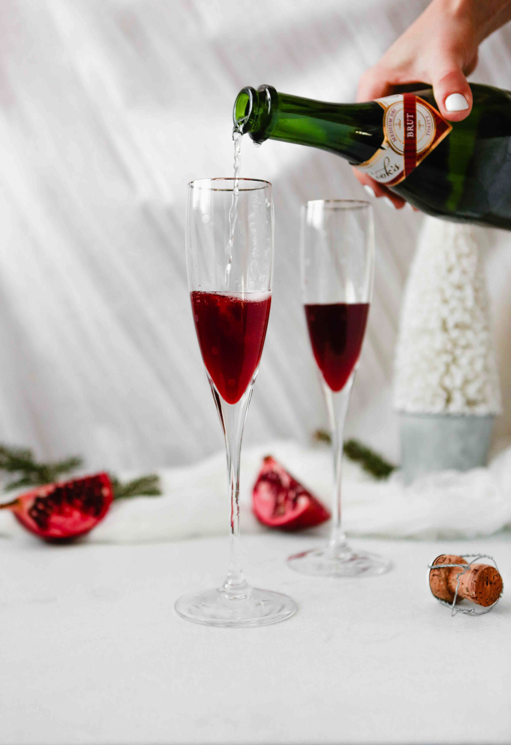 Photograph of sparkling wine being poured into champagne flutes with pomegranate liqueur