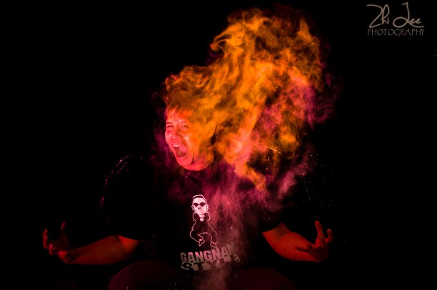 Creative Portrait lit with Fire and Red Flash Against a Black Backdrop. By Zhi Lee