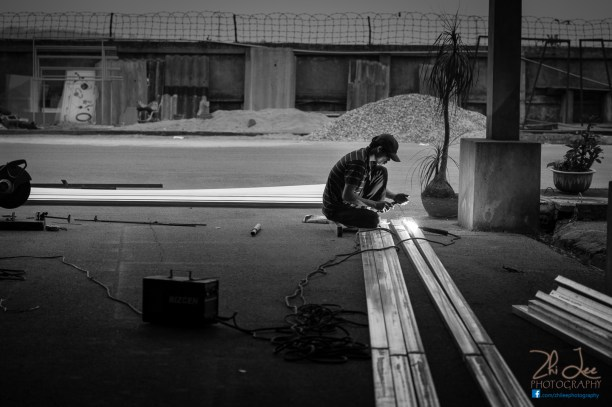A welder in Hanoi uses his hands as a screen. By Zhi Lee