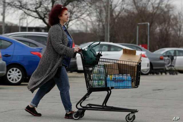A shopper wheels her cart full of groceries in Skokie, Ill., March 14, 2020.