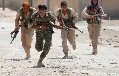 FILE - Kurdish fighters from the People's Protection Units (YPG) run across a street in Raqqa, Syria, July 3, 2017.