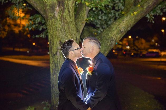 Happy Couple Kissing Under Tree at Wedding