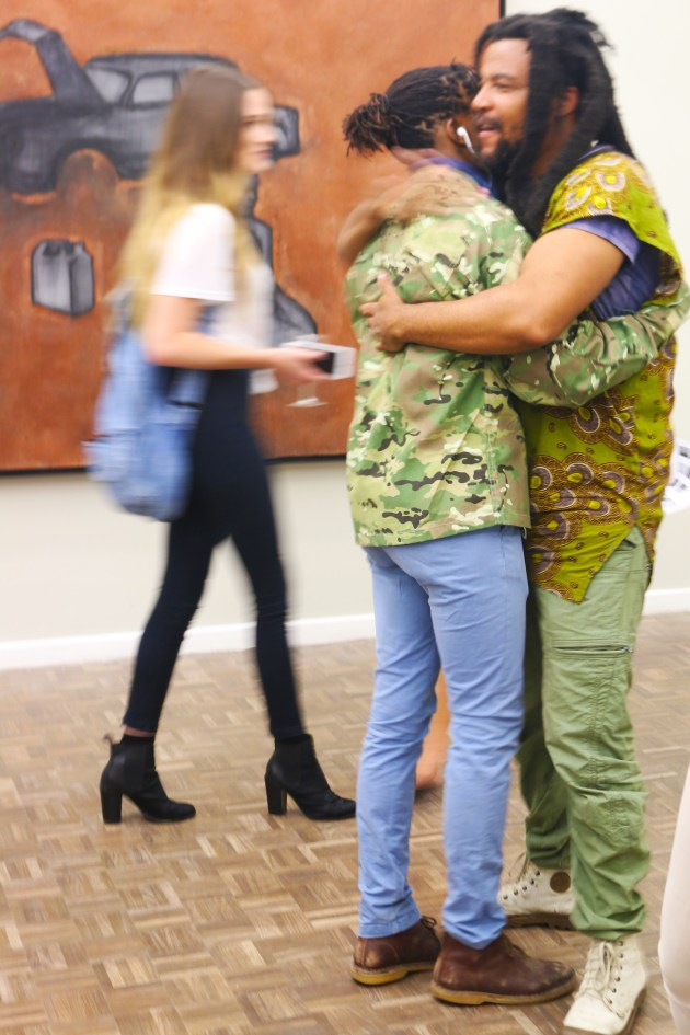 Mawande Ka Zenzile and Ayanda Mabulu embrace after the exhibition.