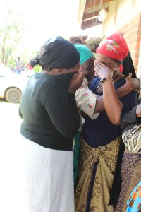 women crying whilst huddled together